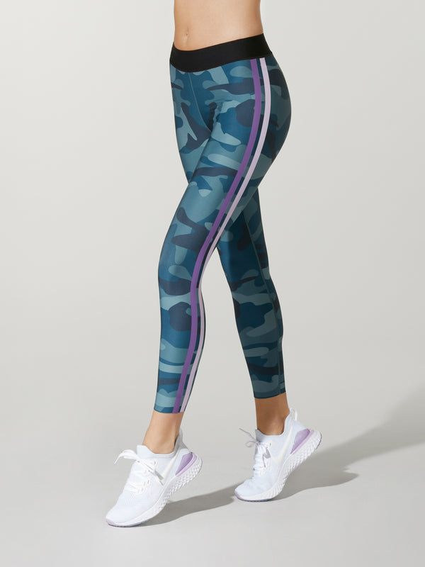 side view of model in blue camouflage leggings with black elastic waistband with pink and white stripe down leg and white sneakers