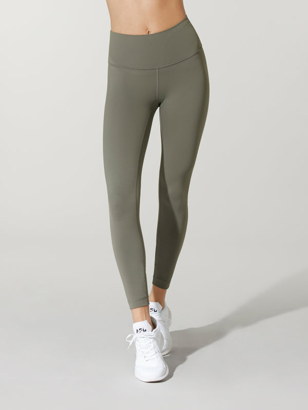 front view of model in olive green leggings and white sneakers