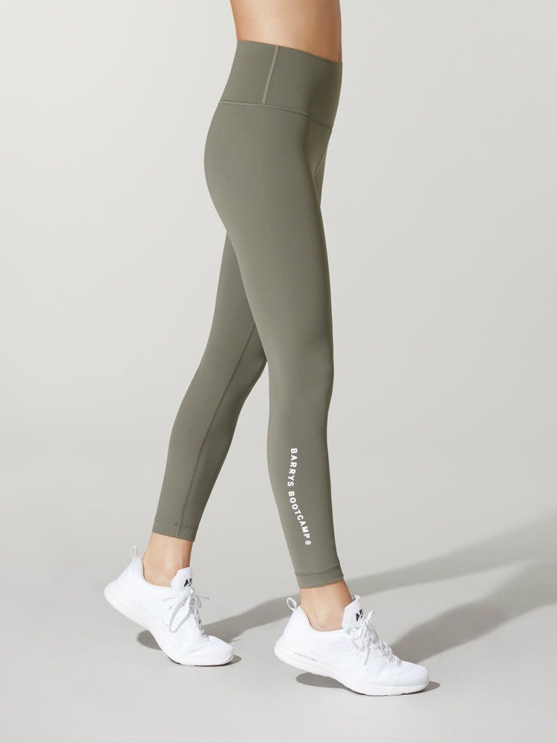side view of model in olive green leggings and white sneakers