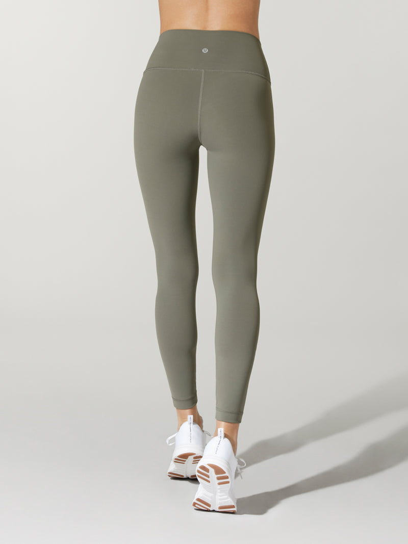 back view of model in olive green leggings and white sneakers