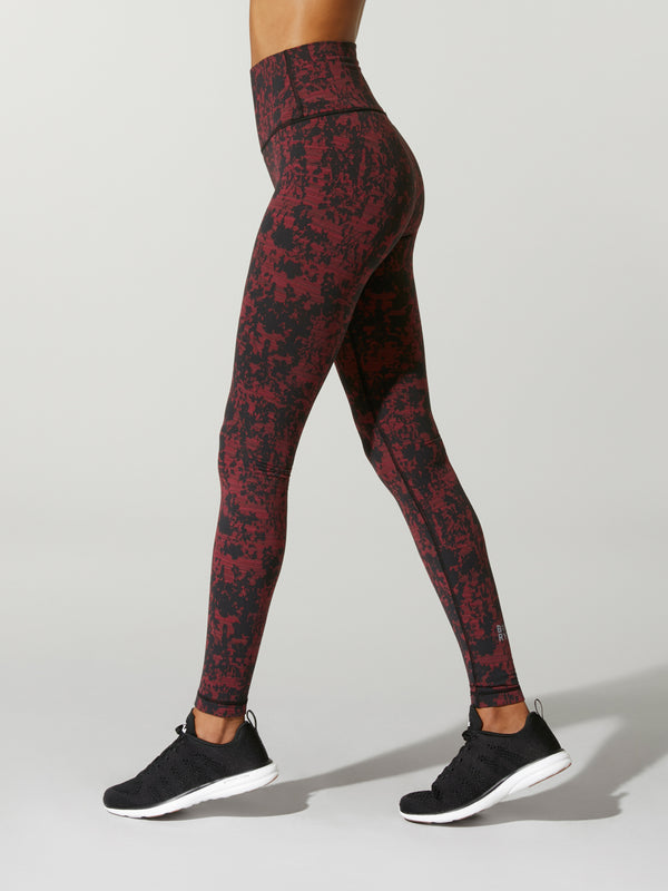 side view of model wearing black and dark red printed leggings and black sneakers
