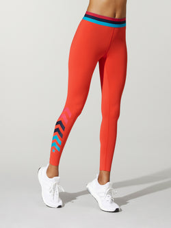 front shot of model wearing Orange FIT FLAME SPRINTER TIGHTs with red and blue waist band and black and blue arrows on the right leg