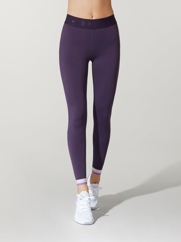 Front shot of model wearing dark purple FIT NIGHTSHADE SPRINTER TIGHTs with black band with barry's logo