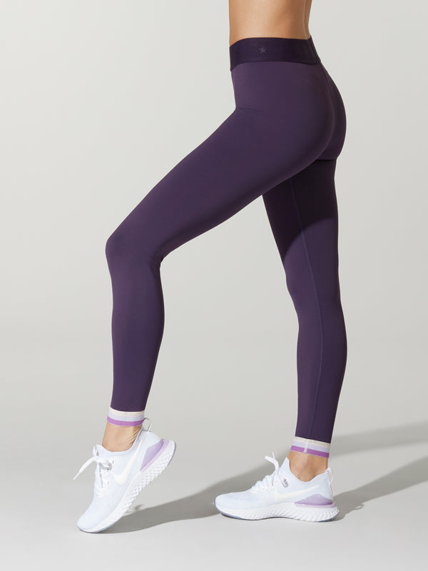 Side shot of model wearing dark purple FIT NIGHTSHADE SPRINTER TIGHTs with black band with barry's logo