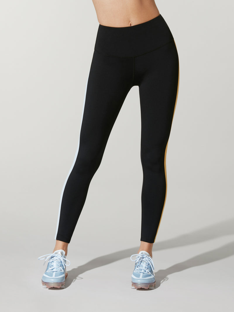 front shot of model wearing black FIT COLORBLOCK SPEED TIGHTs with blue and yellow stripe down the right leg
