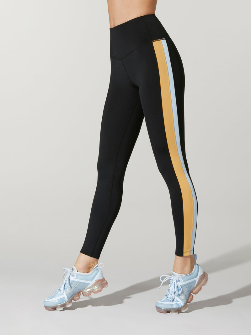 side shot of model wearing black FIT COLORBLOCK SPEED TIGHTs with blue and yellow stripe down the right leg