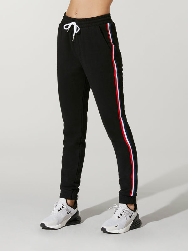 Model wearing black sweatpants with red and white stripe down the side and white drawstring.
