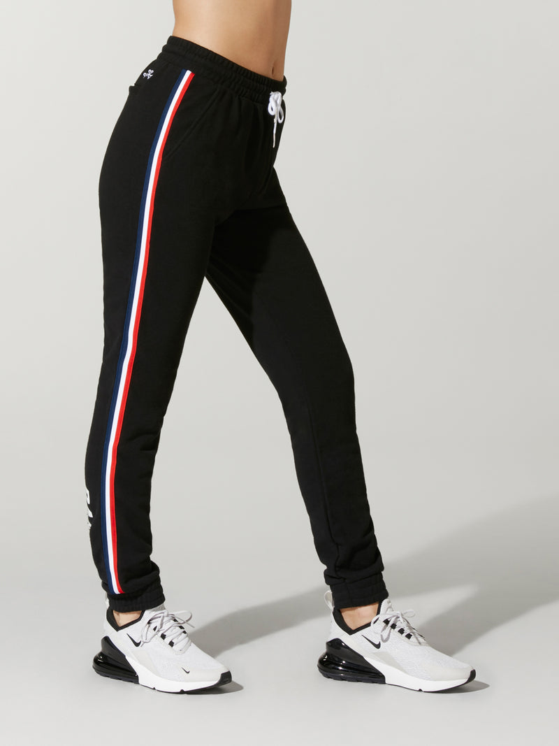 Side view of model wearing black sweatpants with red and white stripe down the side and white drawstring.