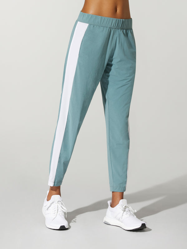 front view of model in teal sweatpants with white stripe down the leg and white sneakers