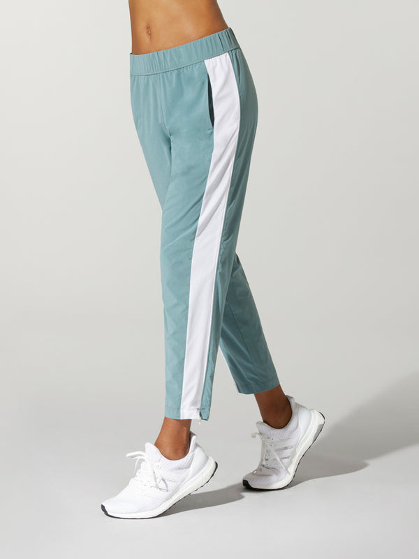 side view of model in teal sweatpants with white stripe down the leg and white sneakers