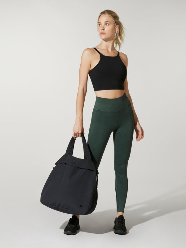 front view of model in black cropped tank and green leggings holding black tote bag