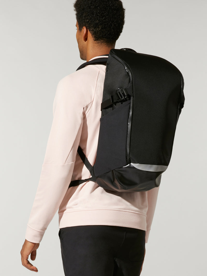 back view of male model wearing light pink sweatshirt and black backpack on back