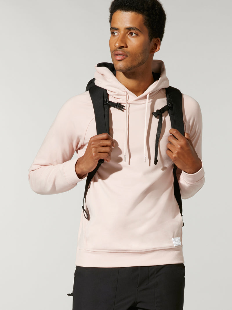front view of male model wearing light pink sweatshirt and black backpack on back