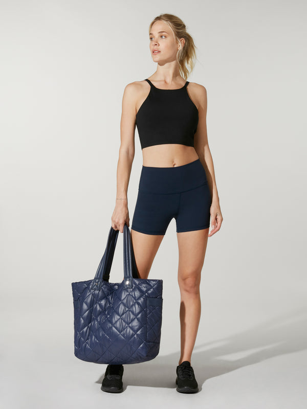 front view of model wearing black crop top and biker shorts holding navy blue tote bag