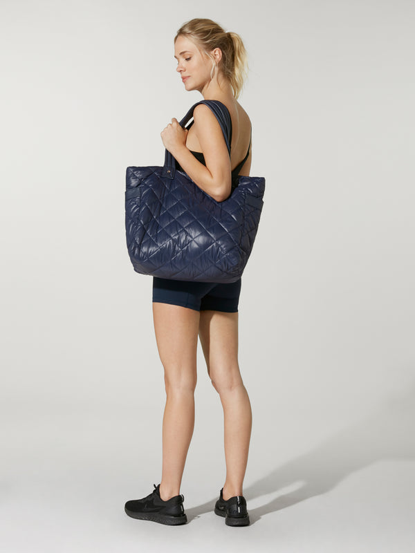 side view of model wearing black crop top and biker shorts holding navy blue tote bag under shoulder