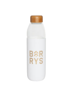 "clear glass water bottle with white rubber saying ""Barry's"" wrapped around middle and wooden top"