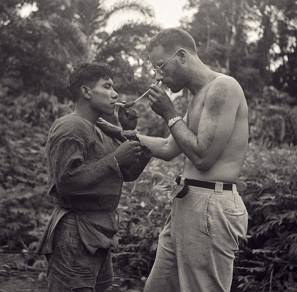 Schultes intaking snuff with help from an Amazonian native