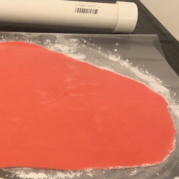 Rolling out rolled buttercream between sheets of vinyl.