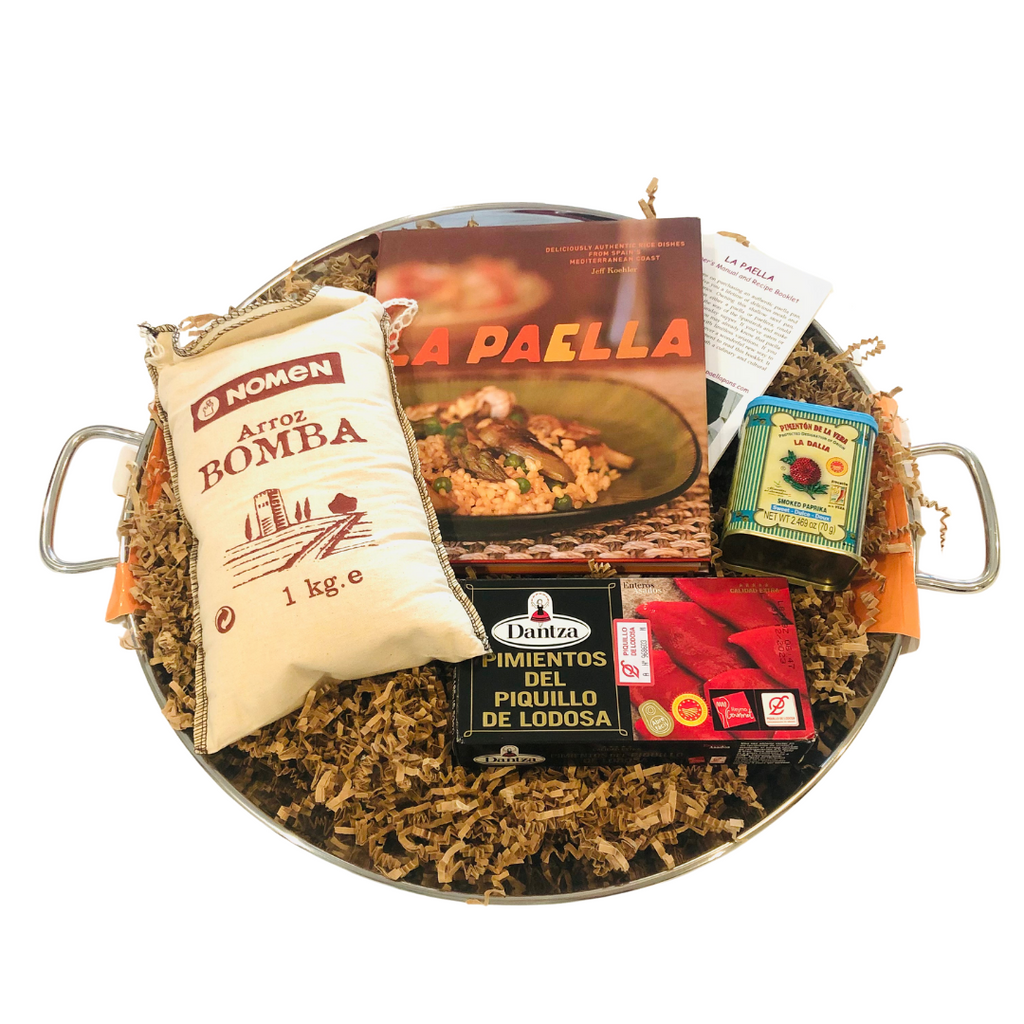 Paella kit in stainless steel paella pan with book, rice, paprika, and peppers
