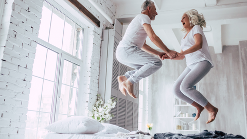 Happy couple jumping on the bed.