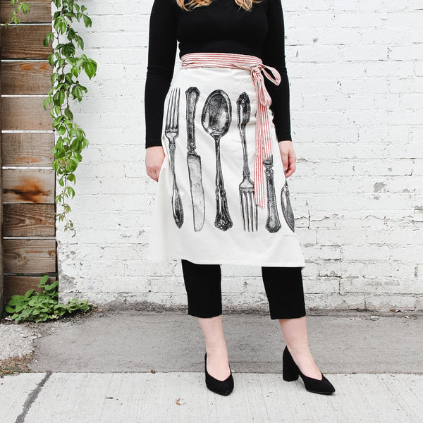 outdoor shot of hester and cook flour sack apron with fork, knife, and spoon. apron is waist-tied and has a red and white striped ribbon tie