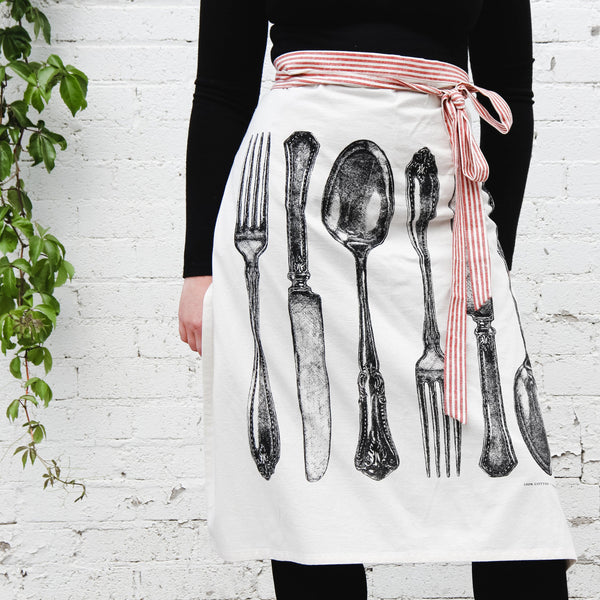 close up shot of hester and cook flour sack apron with fork, knife, and spoon. apron is waist-tied and has a red and white striped ribbon tie