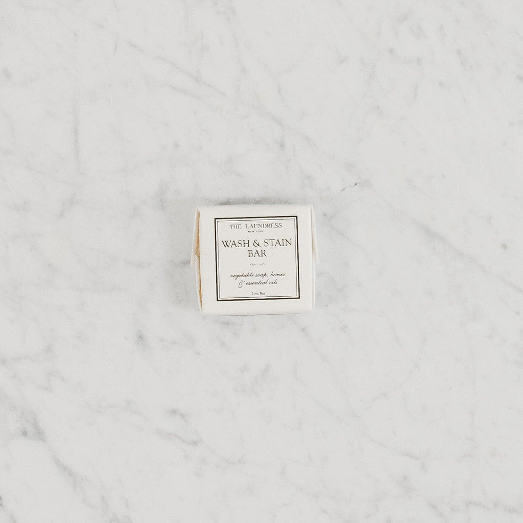 square wash and stain bar soap wrapped in paper packaging by the laundress new york