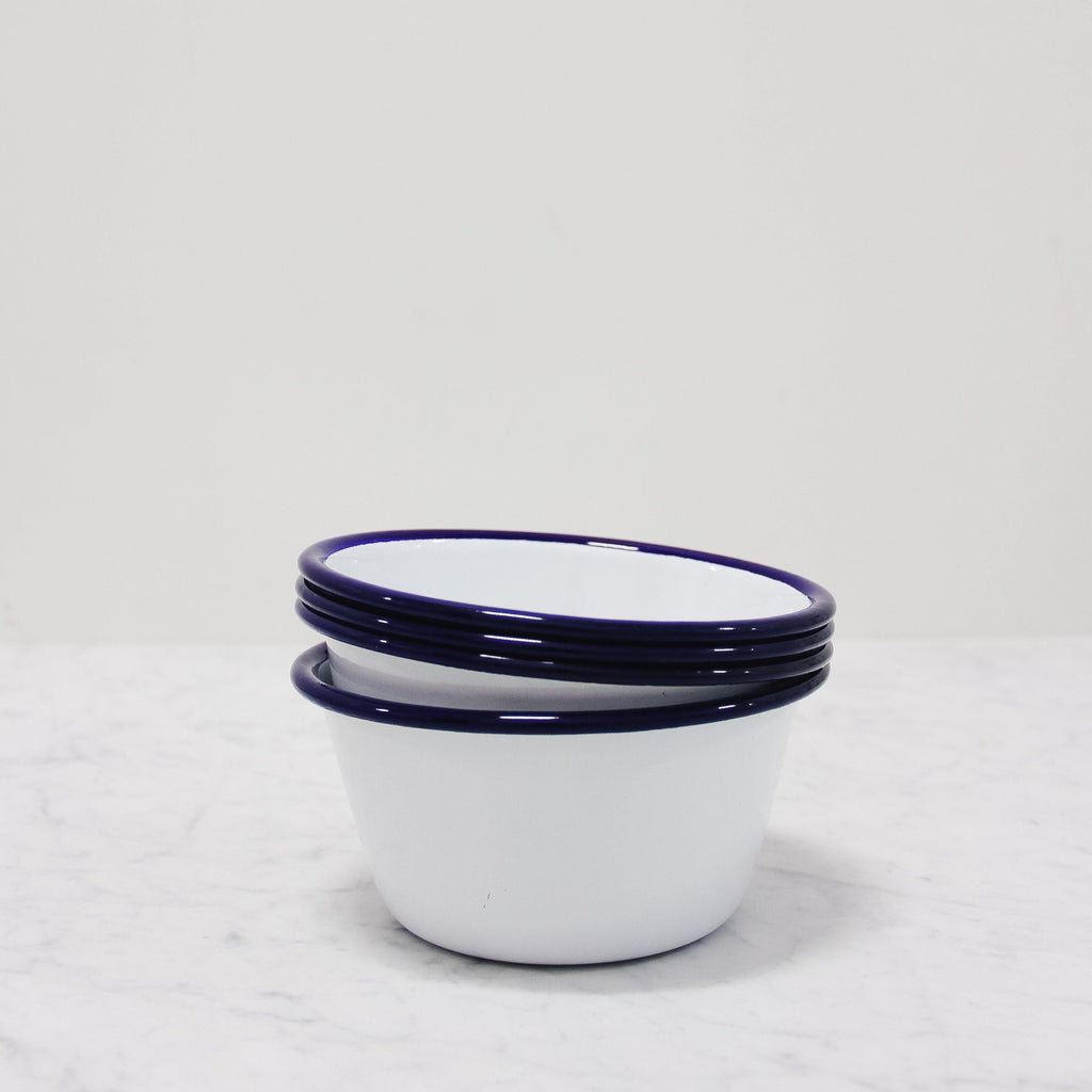 stack of falcon enamelware bowls in white with a blue rim