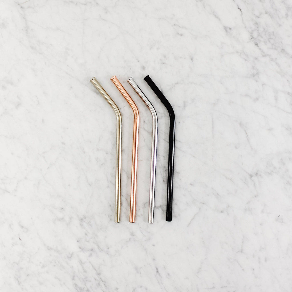 Four metal reusable straws on a marble slab