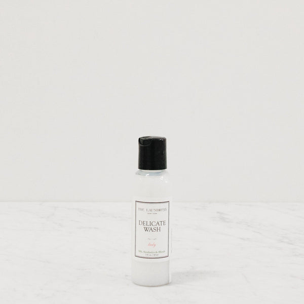travel sized bottle of laundress delicate wash scented laundry detergent