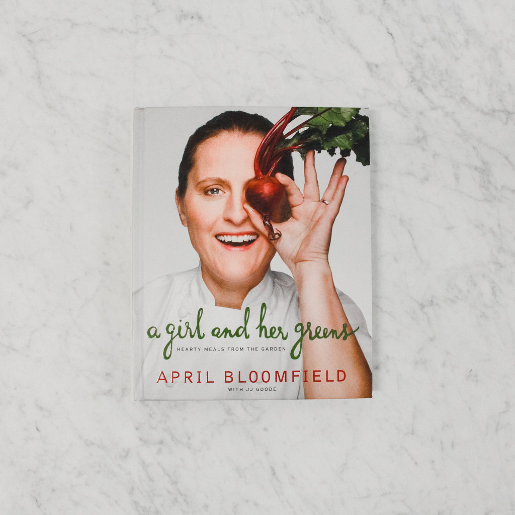 "April Bloomfield titled ""a girl and her greens"" cookbook depicting woman holding a beet over her eye"