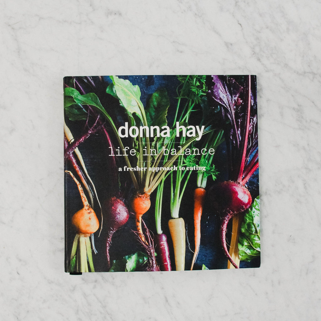 cover of donna hay's life in balance. cover features an assortment of harvested root vegetables against a black background