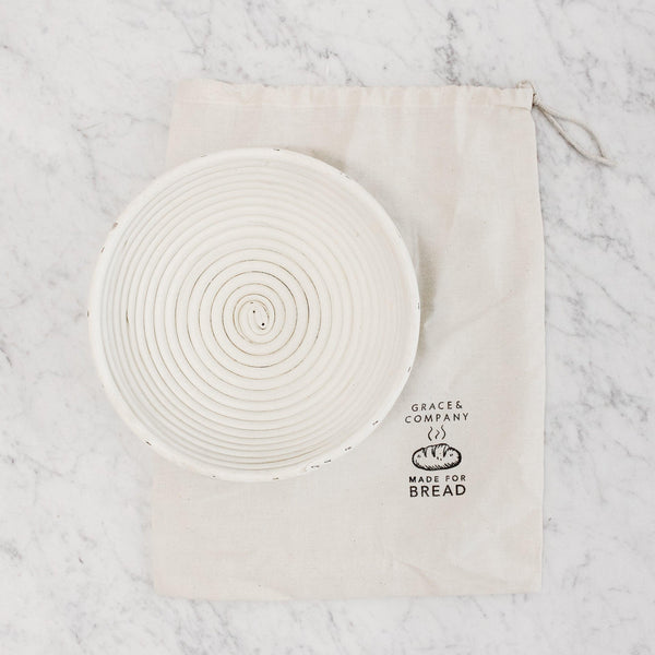 "white brotform round bread proofing basket next to natural colored drawstring bag with a stamp that reads ""grace & company: made for bread"""