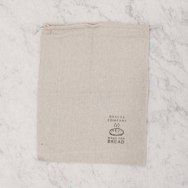 "drawstring muslin bread bag that reads ""grace and company made for bread"""