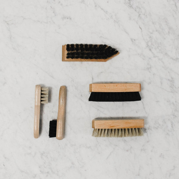 assortment of wooden buffing and polishing brushes arranged on a marble tile