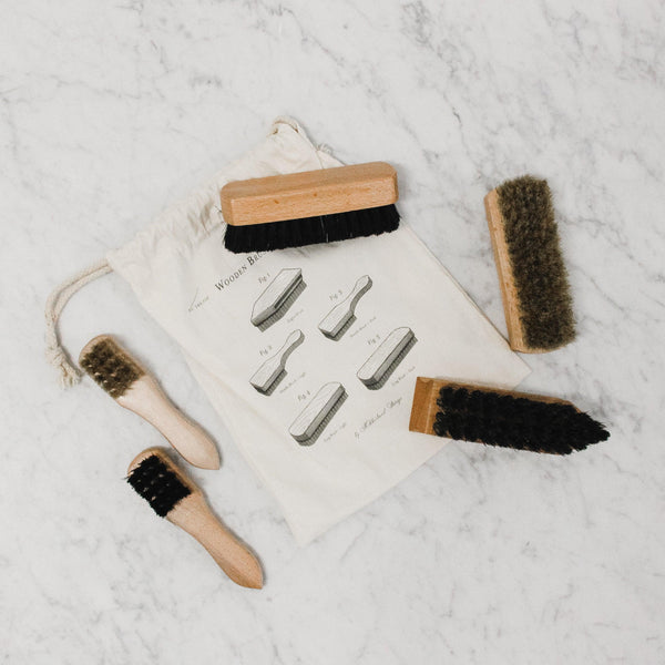 assortment of wooden buffing and polishing brushes with drawstring bag arranged on a marble tile