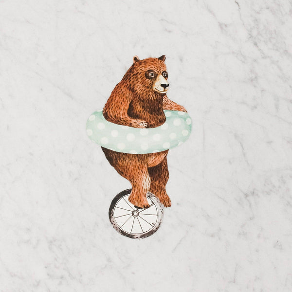 hester & cook table accent featuring a brown bear with an inner tube riding a unicycle