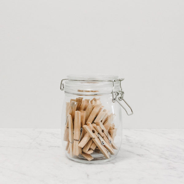 A clear latch lid mason jar filled with clothes pins
