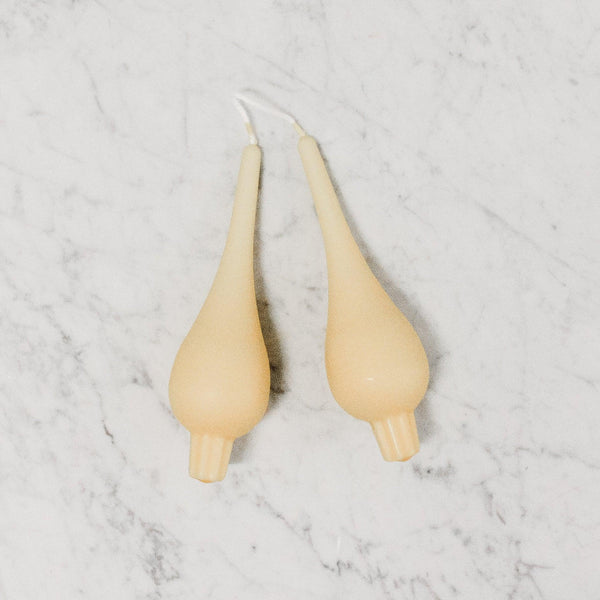 pair of yellow tear drop shaped candle sticks