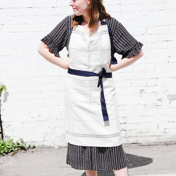 Model shot outdoors against a white brick wall of the Falcon enamelware Natural apron with navy blue thin horizontal stripes and navy ties