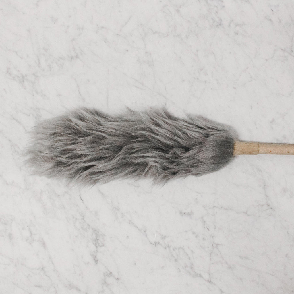 Natural / Grey coloured wool duster with a wood handle.
