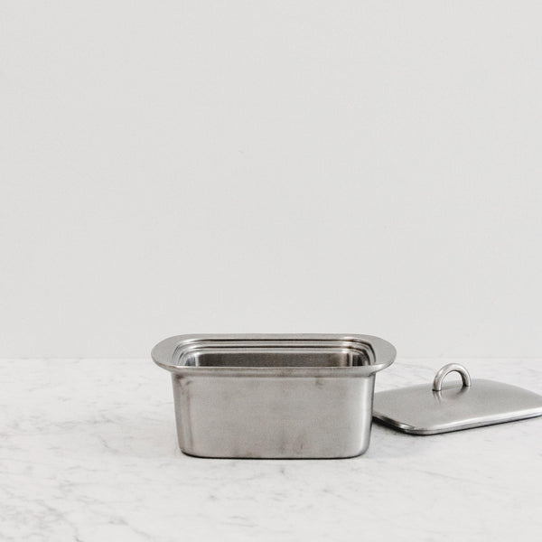 a stainless steel butter box with lid on the side