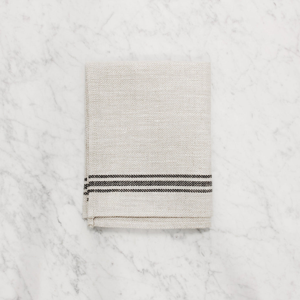 folded linen way luke tea towel in natural with black stripes on edge