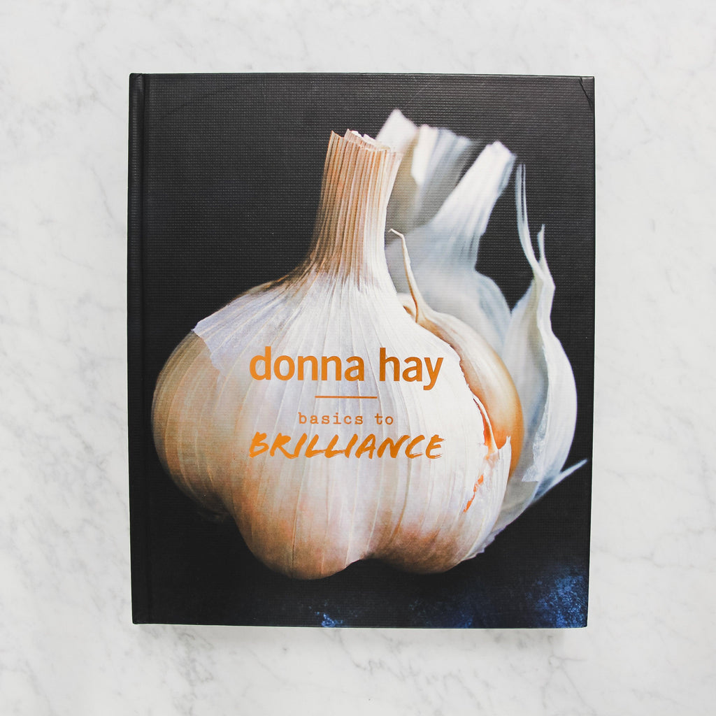 front cover of donna hay's basics to brilliance. cover depicts a large bulb of garlic against a black background with orange text.