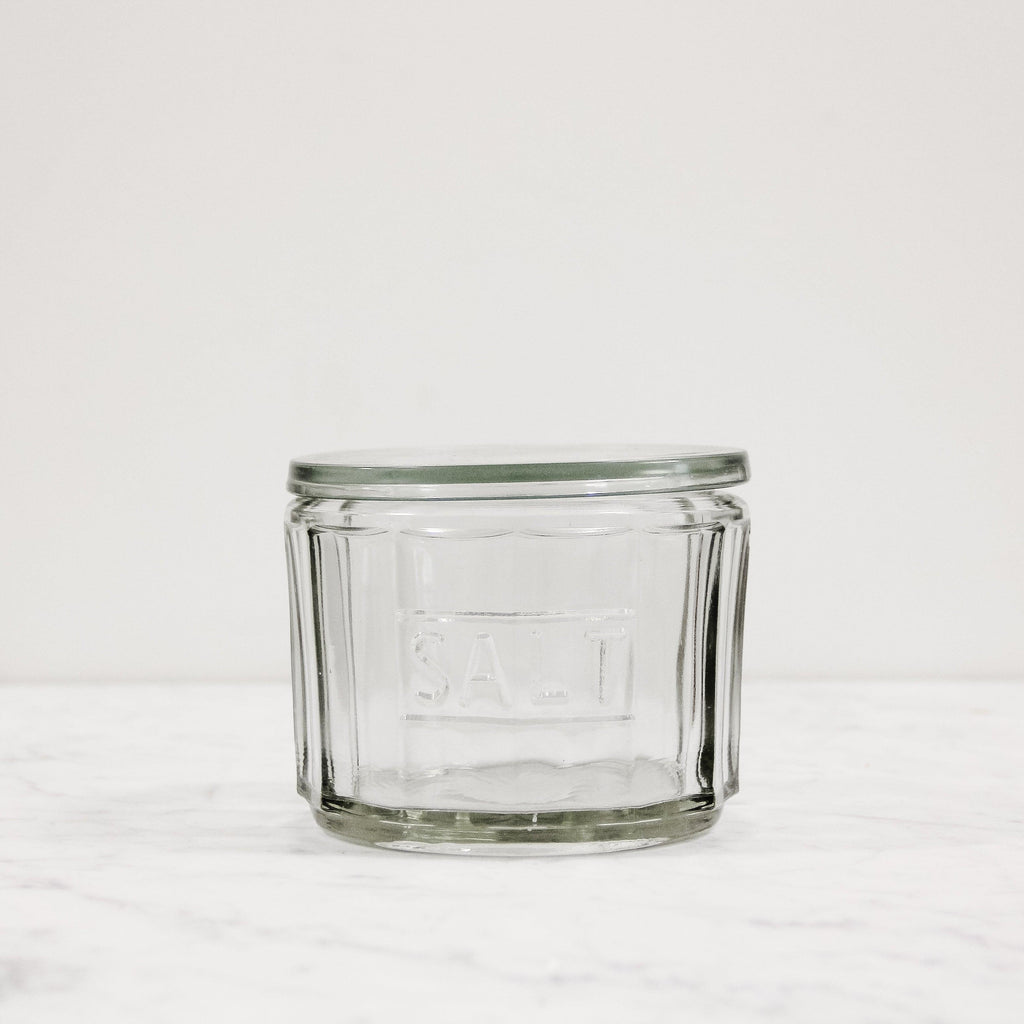 "A glass salt cellar that says ""salt"" embossed in the glass. Has a glass lid"