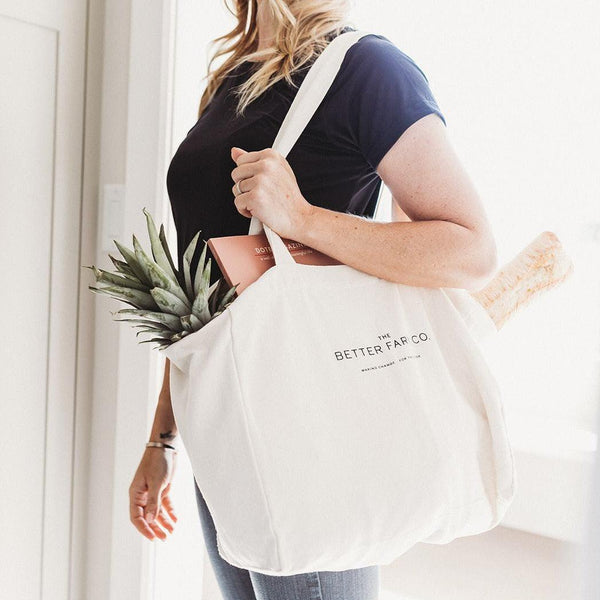 a blonde woman carrying a better farm co canvas tote bag filled with groceries