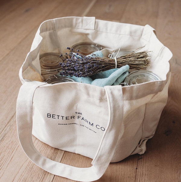better farm co tote bag with internal compartments filled with mason jars and lavender on a wood floor