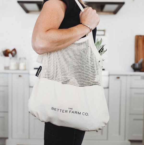 a woman carrying a batter farm co. mesh canvas tote bag over her shoulder in her kitchen