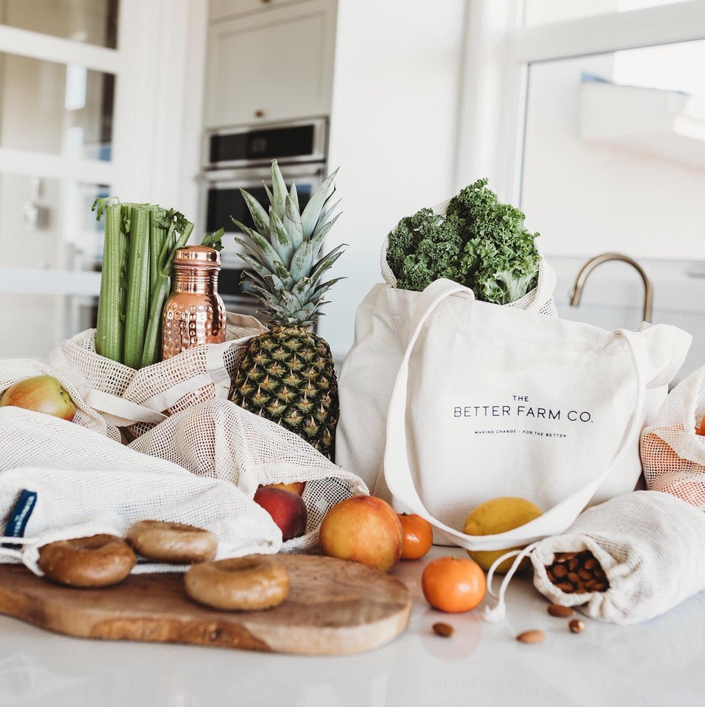canvas tote bags and mesh produce bags filled with various grocery items spread out on a kitchen counter