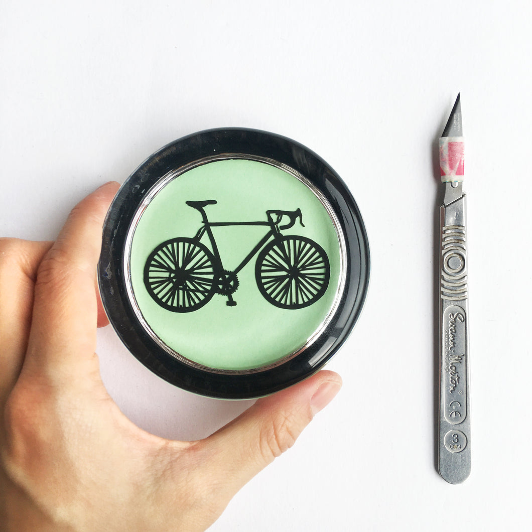 Handcut bike in a glass paperweight
